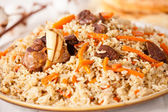 Uzbek national dish pilaf on plate — Stock Photo