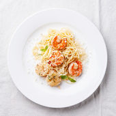 Spaghetti with prawns, sea scallops and basil — Stock Photo
