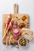 Bread sticks with ham and salami — Stock Photo