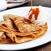 Pancakes crepes with ice cream with caramel sauce — Stock Photo