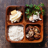 Raw white rice in wooden bowl with ingredients for risotto with — Stock Photo