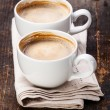 Two cups of coffee on wooden background - Stock Photo