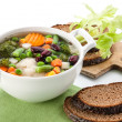 Vegetable soup with bean, pea, carrot and potato in bowl on whit - Stock Photo