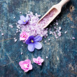 Sea salt on wooden spoon with flowers — Stock Photo #26082807