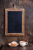 Coffee cup and vintage slate chalk board hanging on wooden backg — Stock Photo