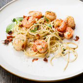 Spaghetti with prawns, sea scallops and parmesan — Stock Photo
