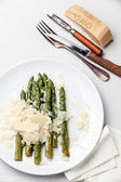 Asparagus with Parmesan cheese on white background — Stock Photo