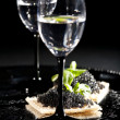 Vodka and sandwiches with black caviar — Stock Photo #30381899
