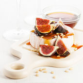 Camembert cheese, figs and honey on light background — Photo