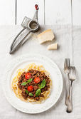 Spaghetti Bolognese on white textured background — Stock Photo