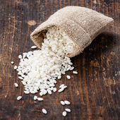 Raw white rice in burlap bag — Stock Photo