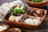 Raw white rice in wooden bowl with ingredients for risotto — Stock Photo