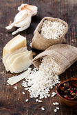 Raw white rice in burlap bag with ingredients for risotto — Stock Photo
