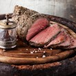 Roast beef on cutting board with saltcellar and pepper mill — Stock Photo #35654929