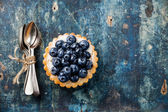 Blueberry tart and Bunch of teaspoons — Stock Photo