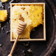 Honeycomb with wooden honey dipper — Stock Photo #36553315
