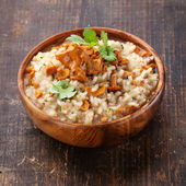 Risotto with chanterelles in wooden bowl — Stock Photo