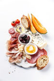 Antipasti ham, cheese, melon, olives, olive oil, bread — Stock Photo
