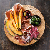 Antipasto ham, melon and olives — Stock Photo