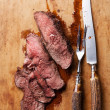 Roast beef with knife and fork — Stock Photo