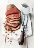 Roast beef with sauce and meat fork — Stock Photo