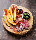 Antipasto snack ham, melon and olives — Stock Photo