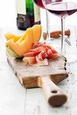Melon cantaloupe with prosciutto ham — Stock Photo