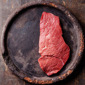 Raw fresh meat Steak on dark wooden background — Stock Photo