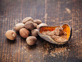 Grated nutmeg on dark wooden background — 图库照片