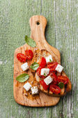 Italian bruschetta with tomatoes, basil and cheese — Stock Photo