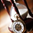 Gold pocket watch and hourglass — Stock Photo #24499759