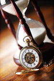 Gold pocket watch and hourglass — Stockfoto