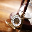 Gold pocket watch and hourglass — Stock Photo #24502845