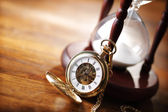 Gold pocket watch and hourglass — 图库照片