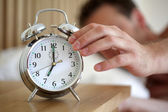Turning off an alarm clock — 图库照片
