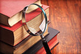 Magnifying glass with old books — Stock Photo