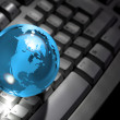 Glass globe on computer keyboard — Stock Photo
