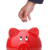 Kind munt invoegen in een piggy bank — Stockfoto