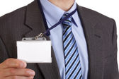Businessman holding blank ID badge — Stock Photo