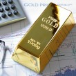 Stock Photo: Gold bullion barr on a stocks and shares chart