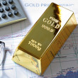Stock Photo: Gold bullion barr on stocks and shares chart