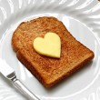 Heart shaped butter on toast - Stock Photo