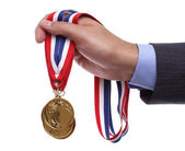 Businessman holding gold medal — Stock Photo
