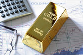 Gold bullion barr on a stocks and shares chart — Stock Photo