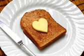 Heart shaped butter on toast — Stock Photo