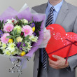 Bouquet of flowers and box of chocolates — Stock Photo