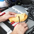 Mechanic checking motor oil - Stock Photo