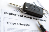 Motor insurance certificate with car key — Photo