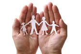 Paper chain family protected in cupped hands — Stockfoto