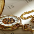 Gold pocket watch and calendar — Stock Photo